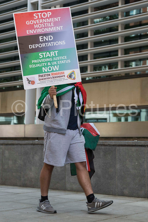 A Windrush campaigner protests outside the Home Office on 23rd June 2021 in London, United Kingdom. A group of campaigners from different groups marched from the Home Office to the House of Commons to deliver a letter calling for a new independent body, and not the Home Office, to administer the scheme intended by the government to compensate them for the violation of their rights. Many legal residents who came to the UK from the Caribbean lost their homes, jobs and other rights after having been targeted by the Home Office.