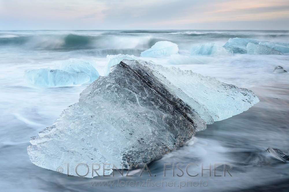 Ice and surf in a long time exposure on the beach of Joekulsarlon at a clear dusk in wintertime, Iceland