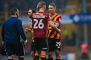 Bradford City defender Matthew Kilgallon (26) is consoled by Bradford City defender Anthony McMahon (29) after getting injured during the EFL Sky Bet League 1 match between Bradford City and Millwall at the Northern Commercials Stadium at Valley Parade, Bradford, England on 21 January 2017. Photo by Simon Davies.