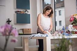 Pregnant woman folding baby clothes in the kitchen, Munich, Bavaria, Germany