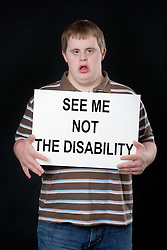Teenage boy with Downs Syndrome holding up a sign,