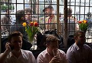 Inside and outside view of customers drinking and socialising at the Newman Arms pub in Fitzrovia, London, UK. Outside drinkers laugh away in the convivial atmosphere of this most traditional of small pubs. The Newman Arms is situated at No. 23 Rathbone Street and was built in 1730. This building has had many functions since that year from housing a tallow chandler, an ironmonger, a picture framers and finally became a brothel. In 1860, the tavern was established and, for the first 100 years, it only possessed a beer licence which explains perfectly the impressive reputation the Newman Arms has for great beer, still firmly intact to this day.