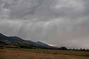 A storm brewing as grey rain clouds empty their water onto the landscape and mountains below on 5th August 2007 in Paradise Valley, near Livingston, Montana. With the Absaroka Rage mountains behind, you can see why Montana has become known as Big Sky Country.