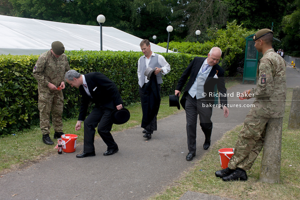 Formally-dressed gentlemen donate coins to soldiers from the Coldstream Guards (from nearby Windsor barracks and deploying to Afghanistan later this year) <br /> during the annual Royal Ascot horseracing festival in Berkshire, England. Royal Ascot is one of Europe's most famous race meetings, and dates back to 1711. Queen Elizabeth and various members of the British Royal Family attend. Held every June, it's one of the main dates on the English sporting calendar and summer social season. Over 300,000 people make the annual visit to Berkshire during Royal Ascot week, making this Europe's best-attended race meeting with over £3m prize money to be won.