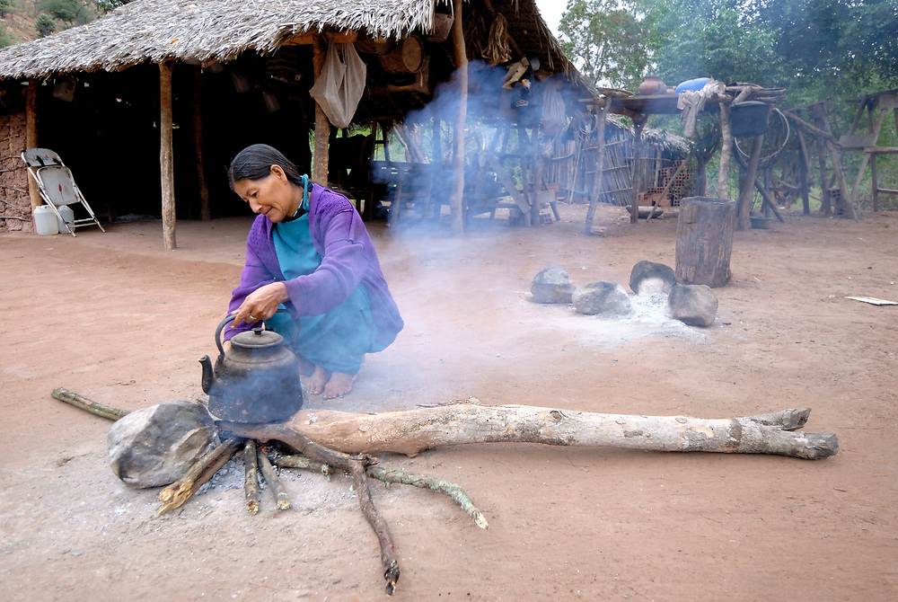 Virginia Centeno, a Guarani indigenous woman, gets hot water heating on her fire in order to make her early morning mate in Naurenda, Bolivia.