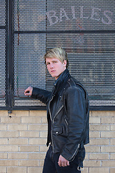All American blond man in a leather jacket by a storefront