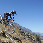 Jordan Shadbolt from Christchurch in action during the NZBNZ South Island Downhill Cup mountain bike downhill series held on The Remarkables face with a stunning backdrop of the Wakatipu Basin. 150 riders took part in the two day event.  Queenstown, Otago, New Zealand. 9th January 2012. Photo Tim Clayton