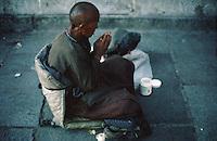 Meditating, a pilgrim sits outside the Jokhang Temple, Lhasa, TIbet.