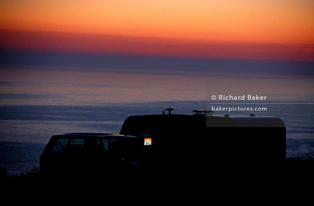 At last light overlooking the sea, a hilltop pitched caravan's TV glows through a window at Trewethett Farm, Cornwall.