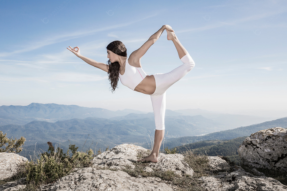 A young woman doing her yoga routines in nature Lord of the dance pose