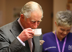 Prince Charles (known as The Duke of Rothesay when in Scotland) has a cup of tea during his visit to the Ayrshire Hospice in Ayr where he met patients and their families, staff and volunteers, with standing-volunteer occupational therapist George Bell (left) and patient Jim Fitzsimmons (centre right) and occupational therapist Joan Carrigan (right).