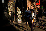 Woman carries boxes past a small girl statue credited to the 19th century Florence-born artist Raffaello Romanelli.