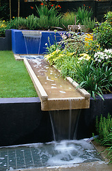 Cascading concrete rill water feature. Protective metal grille. Changing levels.
