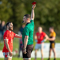 Eire Og's Cathal Lynch is booked by the referee