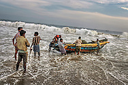 fishermen are bringing a boat through the waves