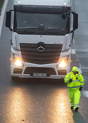 © Licensed to London News Pictures. 21/12/2020. Hollingbourne , UK. A police officer stops and walks a lorry to the hard shoulder, just after junction eight. A major police operation is underway in Kent as Operation Stack is implemented on the M20 due to the Port of Dover and Channel Tunnel having to close in response to France closing its borders to the UK. All freight and passenger traffic have been banned for 48 hours due to the new mutant strain of the Coronavirus in England. traffic. Photo credit:Grant Falvey/LNP