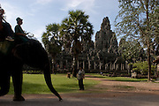 A tourist rides an elephant past Bayon Temple in Angkor complex in Siem Reap, Cambodia.
