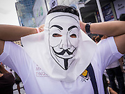 """09 JUNE 2013 - BANGKOK, THAILAND:   A Thai White Mask ties on his Guy Fawkes mask at Central World in Bangkok. The White Mask protesters wear the Guy Fawkes mask popularized by the movie """"V for Vendetta"""" and the protest groups Anonymous and Occupy. Several hundred members of the White Mask movement gathered on the plaza in front of Central World, a large shopping complex at the Ratchaprasong Intersection in Bangkok, to protest against the government of Thai Prime Minister Yingluck Shinawatra. They say that her government is corrupt and is a """"puppet"""" of ousted (and exiled) former PM Thaksin Shinawatra. Thaksin is Yingluck's brother. She was elected in 2011 when her brother endorsed her.    PHOTO BY JACK KURTZ"""