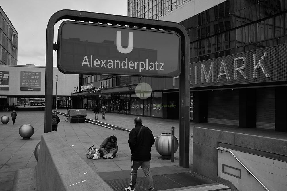 DEUTSCHLAND, Berlin, Alexanderplatz, 20.03.2020. Coronavirus-Pandemie: Wo an normalen Freitagnachmittagen tausende Menschen flanieren und einkaufen gehen, ist es an Tag 5 der der Coronavirus-bedingten Einschränkungen fast leer. Die meisten Geschaefte haben geschlossen, nur wenige Menschen benutzen die oeffentlichen Verkehrsmittel. Ein obdachloser Mann sitzt am U-Bahn-Ausgang.<br /> <br /> Schwarz-Weiss (Original in Farbe).