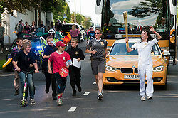 Olympic Torch reaches Sheffield Chapeltown/Ecclesfield/Parson Cross leg.<br /> Torch bearer 106 Katharine Morris accompanied by local Children from Ecclesfield School carries the torch Down Chapeltown Road towards the Common and into Ecclesfield<br /> 25 June 2012.Image © Paul David Drabble