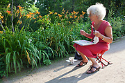 Elderley older German woman painting flowers in the botanical gardens, Berlin, Germany.