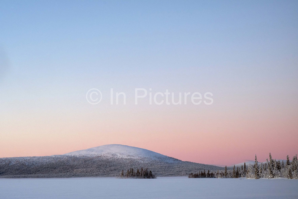 Sunrise over the frozen lake of Jeresjarvi on 20th February 2020 in Finnish Lapland. Jeresjarvi is on the edge of Pallas-Yllastunturi National Park, the third largest national park in Finland and is located in the Lapland region. The natural features and landscape of the fells have always enchanted hikers and the area offers magnificent fells and seemingly endless woodlands.