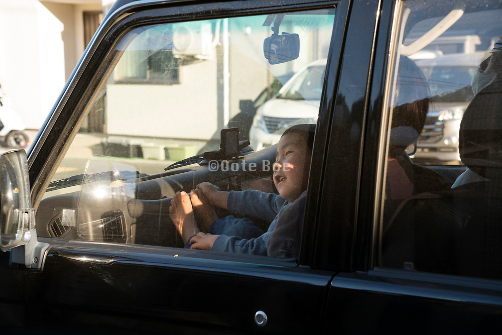 happy Asian child sitting in the front seat of a car