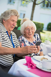 Senior women laughing and looking at smartphone, Bavaria, Germany