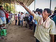 08 FEBRUARY 2014 - PHAWONG, SONGKHLA, THAILAND: A bookie looks for bets during a bullfight in rural Songkhla province, Thailand. Bullfighting is a popular past time in southern Thailand. Hat Yai is the center of Thailand's bullfighting culture. In Thai bullfights, two bulls are placed in an arena and they fight, usually by head butting each other, until one runs away or time is called. Huge amounts of mony are wagered on Thai bullfights - sometimes as much as 2,000,000 Thai Baht ($65,000 US).   PHOTO BY JACK KURTZ