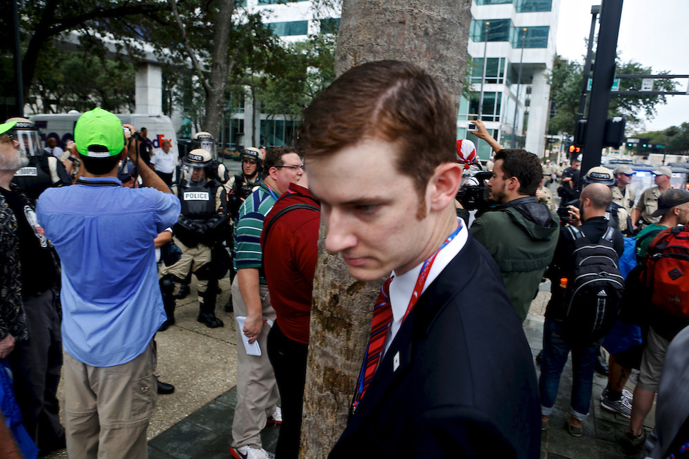 A Mitt Romney suporter walks his way around protesters as they march through the streets during the 2012 Republican National Convention on August, 27, 2012 in Tampa, Fla.