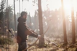 Man shooting with bow and arrow in the forest, Bavaria, Germany