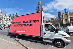 © Licensed to London News Pictures. 17/04/2018. LONDON, UK.  Three vans, each carrying a billboard, with a message protesting against anti-semitism within the Labour party drive around Parliament Square.  Photo credit: Stephen Chung/LNP