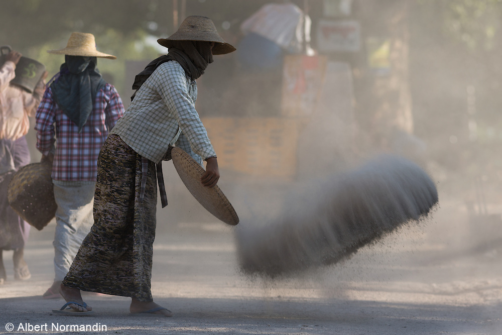 Woman spreading gravel and dust on road under construction, Chindwin Riverbank