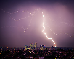 © Licensed to London News Pictures. 19/07/2014. LONDON, UK  Lighting strikes over London's business district, Canary Wharf,  last night, 18th July 2014. The Uk has experienced lightning storms over the last two night with temperatures reaching over 30 degree Celsius.  Photo credit : Andrew Steele/LNP