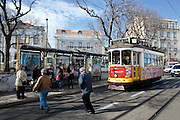 Some passengers run at Graça square, to catch Lisbon's nº28 yellow tram on his way through the central, most historic region of the city.