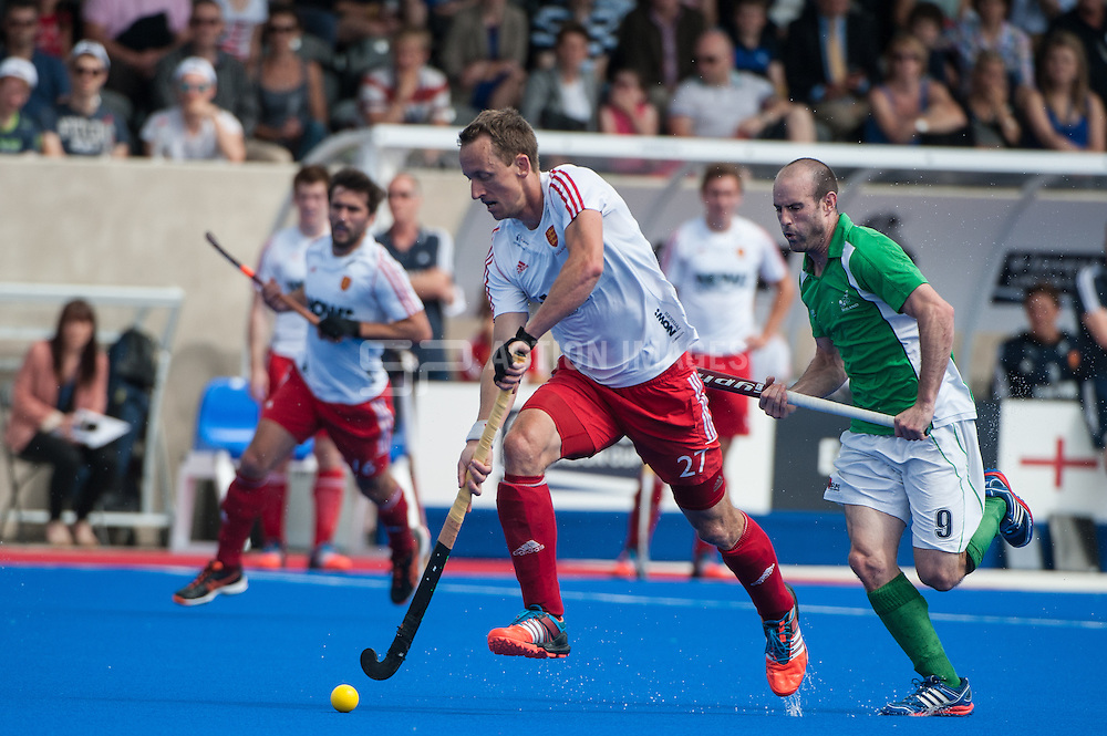 Dan Fox (ENG) drives into the Irish half. Final of the Investec London Cup, Lee Valley Hockey & Tennis Centre, London, UK on 13 July 2014. Photo: Simon Parker