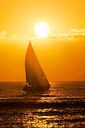 A sailboat sails into the setting sun in Waikiki, Hawaii