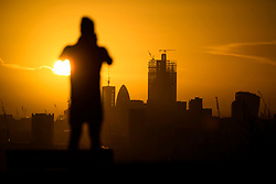 © Licensed to London News Pictures. 16/12/2018. London, UK. A man takes a picture of the sun rising over the City of London, seen from Parliament hill on Hampstead Heath, on a cold winter morning.  Large parts of the UK have experienced snowfall as storm Deidre brings freezing temperatures. Photo credit: Ben Cawthra/LNP
