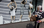 Woman shopper walks past stripe-themed shop window display. Stripes are a style for 2015 and Britain's fashion windows are seemingly full of such designs for the stylish to consider when out buying high street clothes. Three manneqiuins stand in the window of this Oxford Street shop. The woman walking past however, wears a much wider stripe to the models and background of the display.