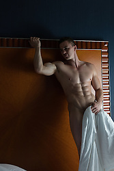 nude muscular man in a bedroom holding a sheet