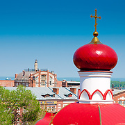 The beautiful red dome of the Iversky nunnery (monastery) in Samara with the brewery on background