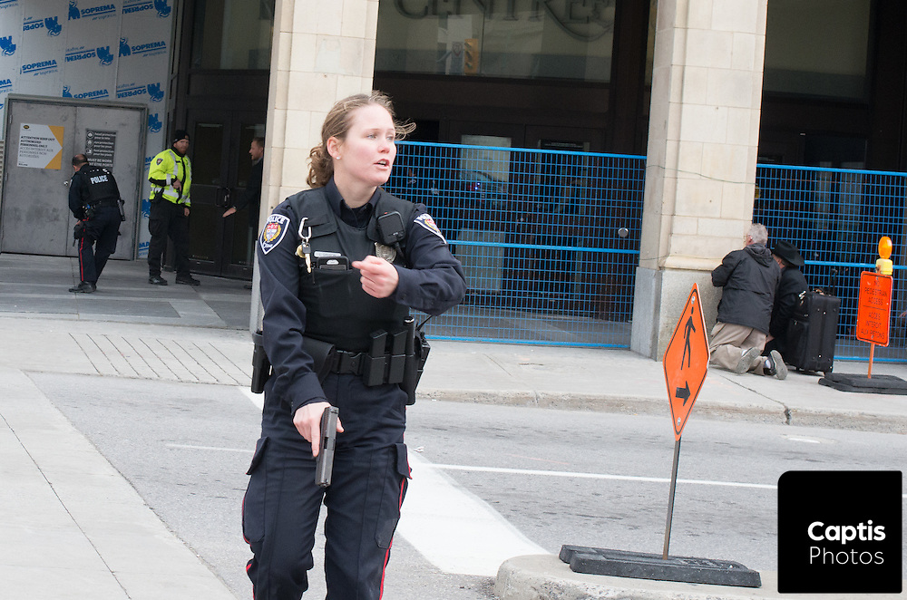 A police officer yells at people to move while police armed with assault rifles enter the Rideau Centre shopping mall. The mall was placed under lock down following the shooting of Cpl. Nathan Cirillo minutes away at the National War Memorial. October 22, 2014.