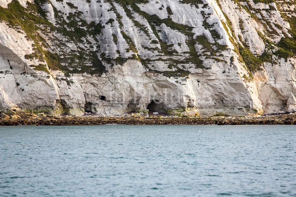 Naturally occurring sea caves long the chalk cliffs above The Warren beach, near Folkestone, Kent, England, United Kingdom.