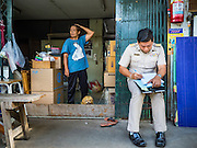 16 OCTOBER 2015 - BANGKOK, THAILAND:  A woman being evicted from her home waits for a Thai government official to complete her eviction paperwork in the Wat Kalayanamit neighborhood. Fifty-four homes around Wat Kalayanamit, a historic Buddhist temple on the Chao Phraya River in the Thonburi section of Bangkok, are being razed and the residents evicted to make way for new development at the temple. The abbot of the temple said he was evicting the residents, who have lived on the temple grounds for generations, because their homes are unsafe and because he wants to improve the temple grounds. The evictions are a part of a Bangkok trend, especially along the Chao Phraya River and BTS light rail lines. Low income people are being evicted from their long time homes to make way for urban renewal.   PHOTO BY JACK KURTZ