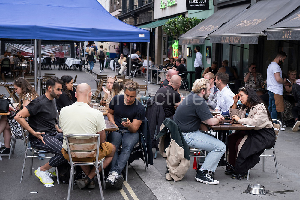 As the national coronavirus lockdown three eases towards the planned Freedom Day in just over two weeks, people eating a socialising outdoors at restaurant and bar tables on Old Compton Street in Soho on 3rd July 2021 in London, United Kingdom. Now that the roadmap for coming out of the national lockdown and easing of restrictions is set, dome medical professionals are suggesting thatsome safety measures are kept in place because of the increase in the Delta variant.