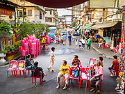 18 JANUARY 2015 - BANGKOK, THAILAND: Spectators gather on Chulalongkorn Soi 7 before the Sai Yong Hong Opera Troupe performance at the Chaomae Thapthim Shrine, a Chinese shrine in a working class neighborhood of Bangkok near the Chulalongkorn University campus. The troupe's nine night performance at the shrine is an annual tradition and is the start of the Lunar New Year celebrations in the neighborhood. The performance is the shrine's way of thanking the Gods for making the year that is ending a successful one. Lunar New Year, also called Chinese New Year, is officially February 19 this year. Teochew opera is a form of Chinese opera that is popular in Thailand and Malaysia.             PHOTO BY JACK KURTZ