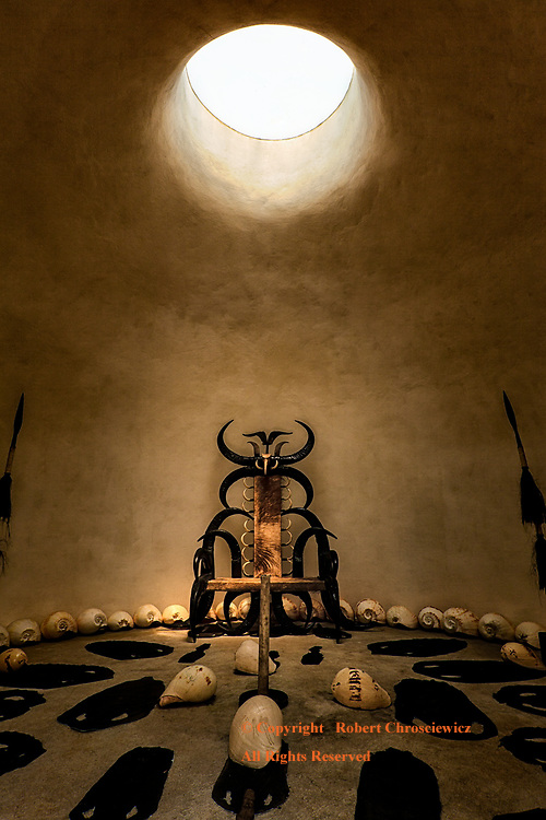 Throne: A circular sky light cast light down upon the throne made of exotic woods and horns; the room itself is decorated with a distinctively African influence, with animal skins, large sea shells and spears, in the Black House, Chiang Rai Thailand.