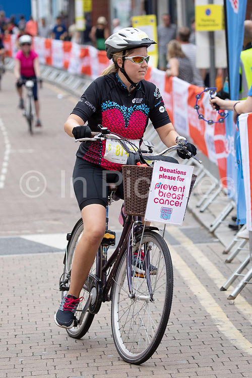 A female cyclist with a Prevent Breast Cancer donations basket cycles during the 7th Prudential RideLondon Surrey Classic on the 4th August 2019 in Kingston upon Thames in the United Kingdom.