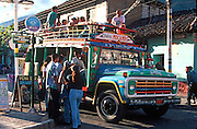 ECUADOR, HIGHLANDS, BANOS hot springs resort; teens boarding bus
