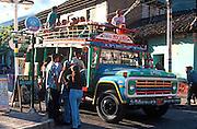 ECUADOR, HIGHLANDS, BANOS hot springs resort; teens boarding bus